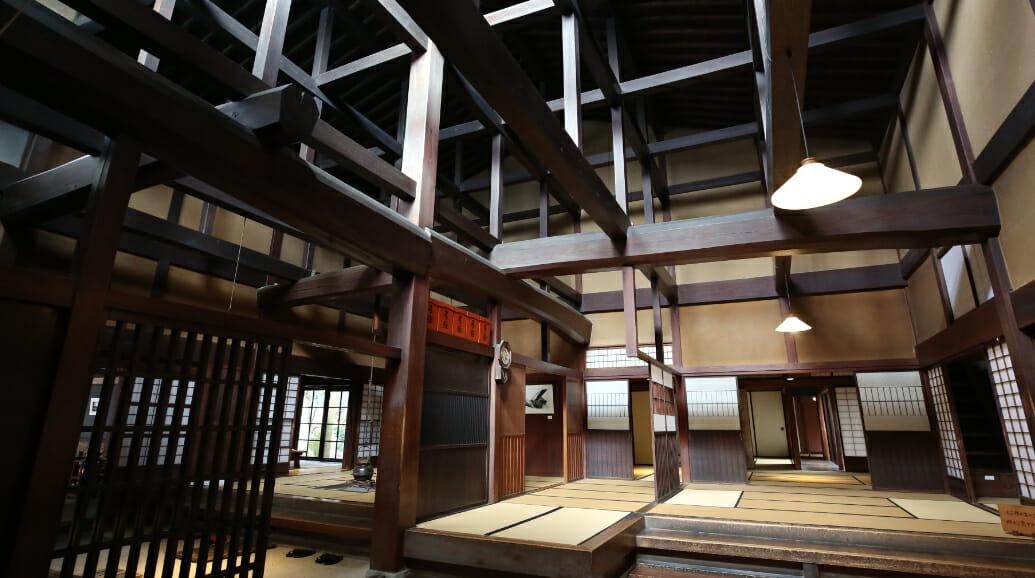 大黒柱を中心に、梁(横にかける材)と束(梁に垂直の短い柱)によって構成される吹き抜けは、高窓からの光線をたくみに屋内に取り入れ、柱や鏡戸の木目を美しく見せています。